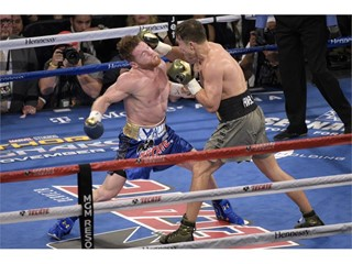 Gennady Golovkin (gray trunks) hits Canelo Alvarez with a right