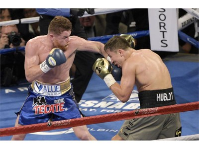 Gennady Golovkin (gray trunks) is hit with a left from Canelo Alvarez