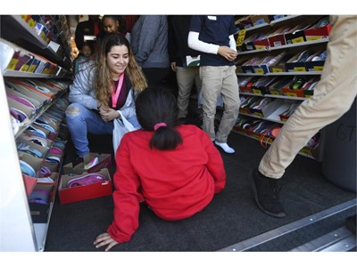 Volunteer Silvia Florez helps fit a student's shoes