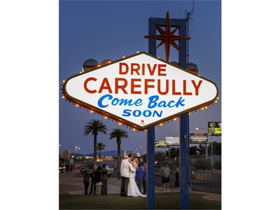 A bride and groom pose for photos at the Welcome to Fabulous Las Vegas sign