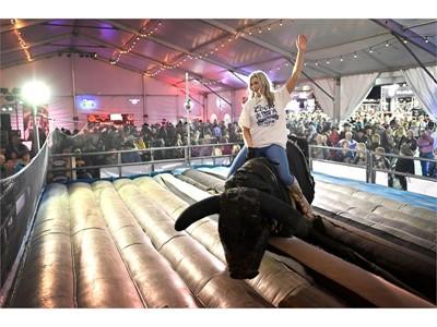Fan Zone: Megan Viterbo of Arizona rides a mechanical bull
