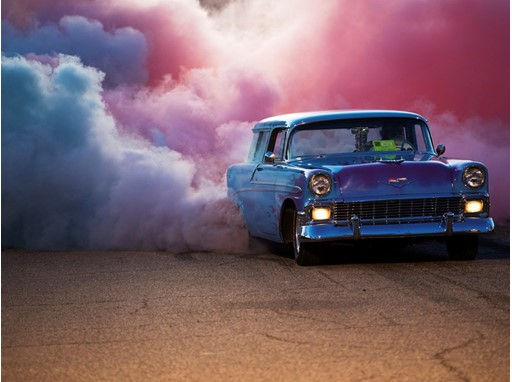 Reg Bennion sends up clouds of red and blue smoke from the tires of his 1956 Chevrolet Nomad