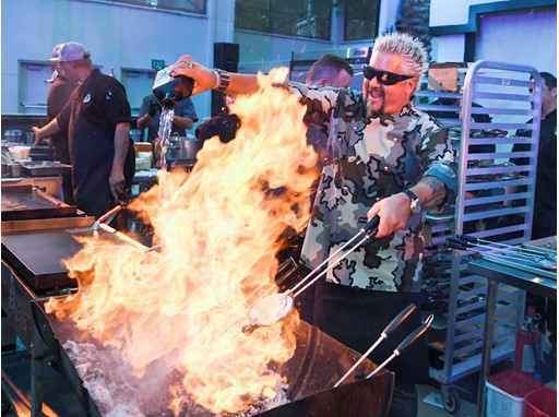 Guy Fieri pours tequila on a charcoal fire
