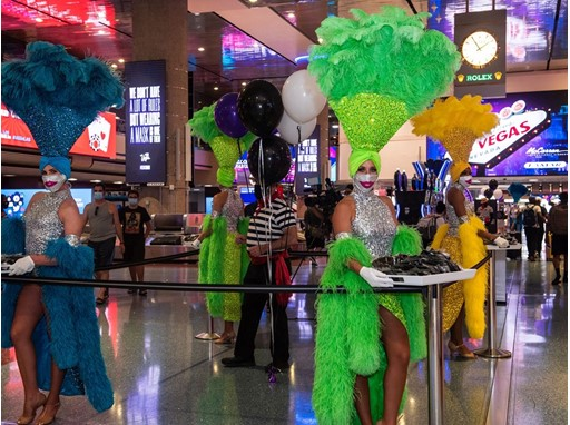 Las Vegas Showgirls and a Venetian Las Vegas Gondolier hand out masks at McCarran International Airport June 26, 2020