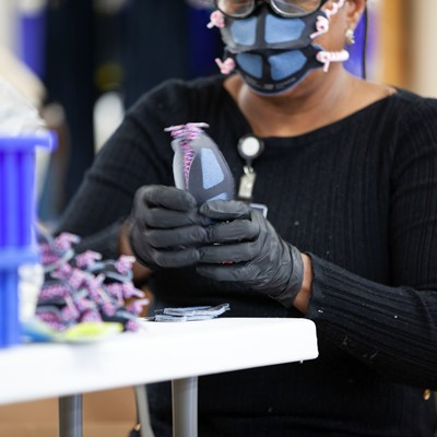 New Balance associate using and inspecting face masks at the company's Lawrence, MA factory.