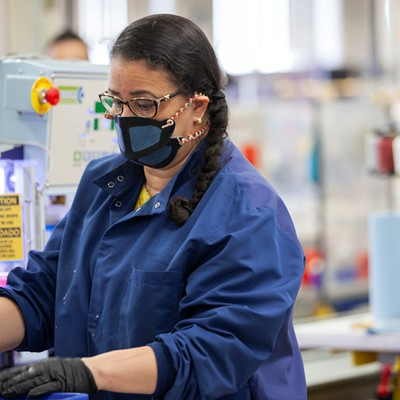 New Balance associate using and fabricating face masks at the company's Lawrence, MA factory.