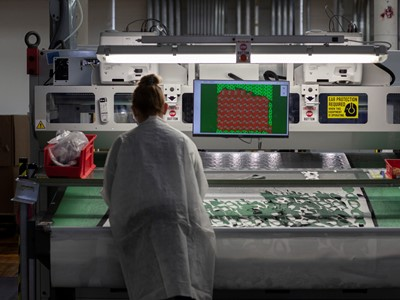 New Balance associate at its Lawrence, MA factory fabricating face masks. The company estimates it will produce 100,000