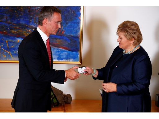 Former Norwegian Prime Minister, Mr Jens Stoltenberg, formally hands over the keys to the PM's office to Ms Erna Solberg