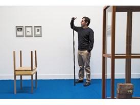 "Mateo López surveys his exhibition ""Avenida Primavera, Casa No. 2"" at Galeria Casas Riegner in Bogota. The burnt wooden"