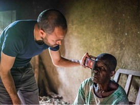 Laureate Andrew Bastawrous uses the Peek device to examine a Kenyan woman suffering from cataracts.