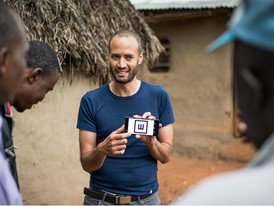 Andrew Bastawrous (centre) uses Peek to check a Kenyan man's sight (right).