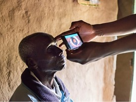 In a remote Kenyan village Isaac Busieney's retina is examined using Peek's mobile technology.