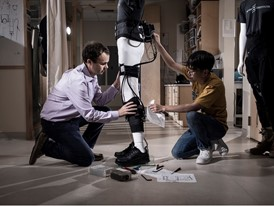 Laureate Conor Walsh (left) and a colleague assemble an exosuit on a mannequin.