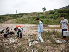 Christine Keung (left) and colleagues examine rubbish dumped beside a river near Yanan, China.