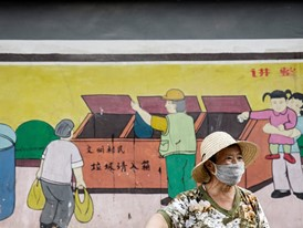 A sanitation worker in front of a street display illustrating disposal methods in Xiangjisi village, Xi'an, China.
