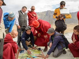Sonam Wangchuk shows building plans to monks and colleagues at the planned site for a university.