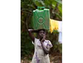 Agnes Nandagire Balances a Full Jerry Can on her Head on her Way Home from Collecting Water