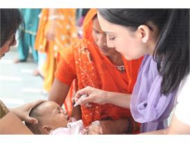 Actress and Rotary polio ambassador Archie Panjabi visits with young children at a health clinic in New Delhi, India