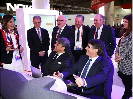Catalan President Carles Puigdemont sitting in SEAT simulator with Luca de Meo, accompanied by Catalan Minister of Busin