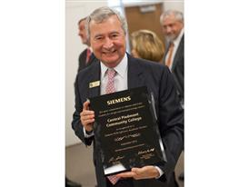 Central Piedmont Community College president Dr. Tony Zeiss holds a plaque commemorating the grant from Siemens 9/24/14