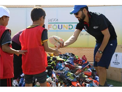 Children at the Zaatari Refugee Camp receive donated football boots from 2018/2019 season Trophy Tour Driven by Kia camp